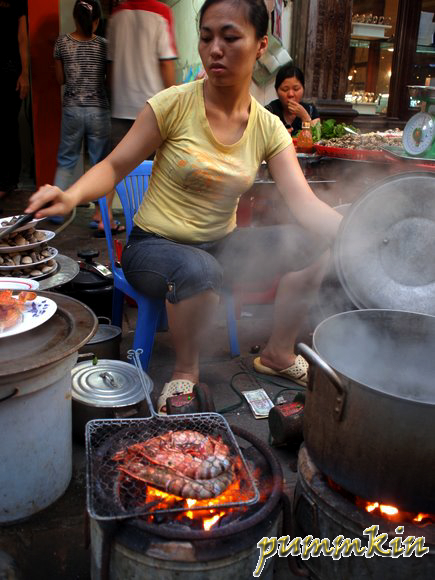 Woman preparing shellfish & grilling over fire in the streets of Hanoi, Vietnam.